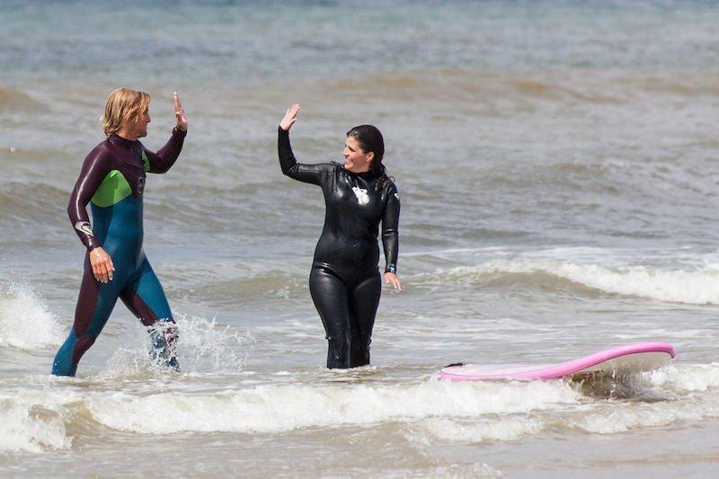 Surf lehr ist im wasser mit surfboard und surfer