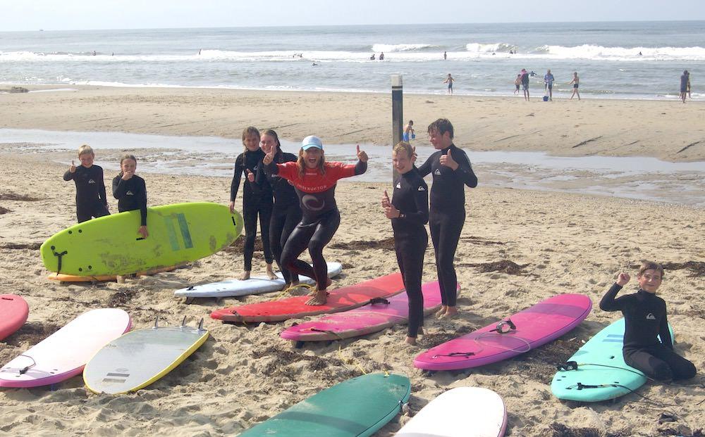 Kids juichen met instructeur tijdens de surfles
