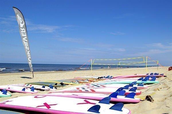 Surfboards liggen op het strand volleybal net staat