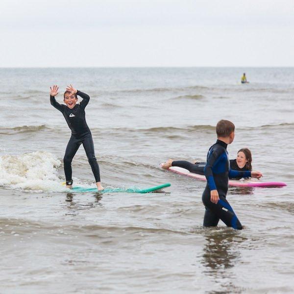 Surfer juicht met zijn handen omhoog op een golf tijdens de surfles