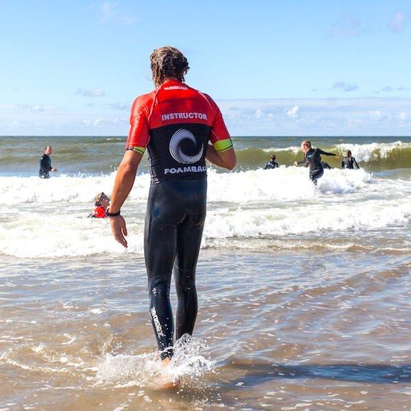 Surfleraar surfschool Foamball staat in het water tijdens de surfles