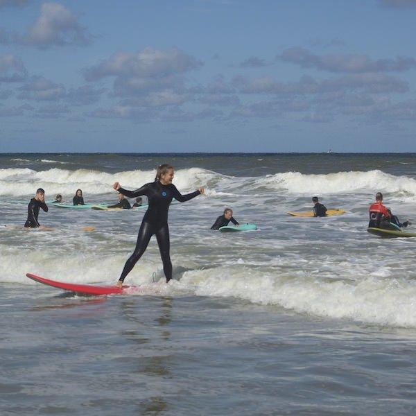 Surf dame juicht staand op haar surfboard op een golf tijdens de surfles