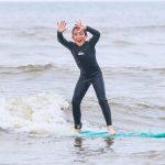 Een surfer juicht tijdens de surfles