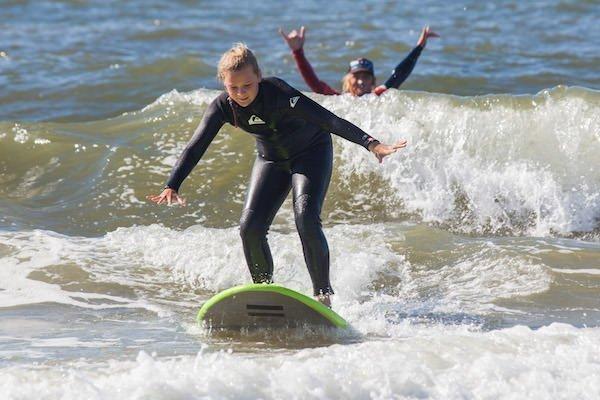Surfles op Texel surfleraar juicht op de achtergrond