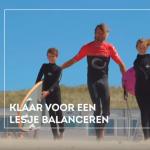 Surf instructor loopt met kids naar de zee voor landal greenparc reclame