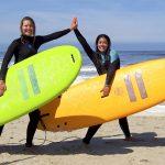 Surf meiden met surfboard geven elkaar een high five